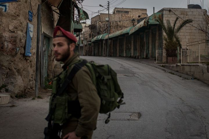 An Israeli soldier stands guard at a checkpoint on a street that separates an Israeli settlement and a Palestinian neighborho