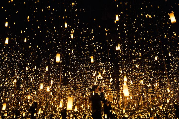 """A woman photographs inside the """"Aftermath of Obliteration of Eternity"""" infinity room."""