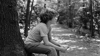 1970s SIDE VIEW OF BOY SITTING AT FOOT OF TREE ALONG TRAIL IN WOODS  (Photo by H. Armstrong Roberts/ClassicStock/Getty Images)
