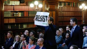 "An environmental activist holds a banner reading ""resist"" while attending a speech by Myron Ebell (L), who leads U.S. President Donald Trump's Environmental Protection Agency's transition team, at the Solvay library in Brussels, Belgium February 1, 2017. REUTERS/Yves Herman"