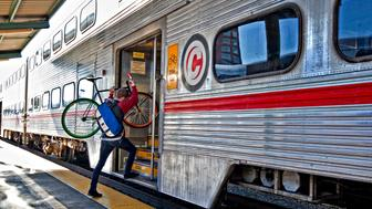 A commuter carries his bicycle aboard a Caltrain train in San Francisco, California, U.S., on Monday, Nov. 24, 2009. Caltrain and the California High-Speed Rail Authority have formed a partnership called the Peninsula Rail Program, which is jointly facilitating improvements to Caltrain under the Caltrain 2025 plan to bring high-speed rail to the Peninsula. Photographer: Chip Chipman/Bloomberg via Getty Images