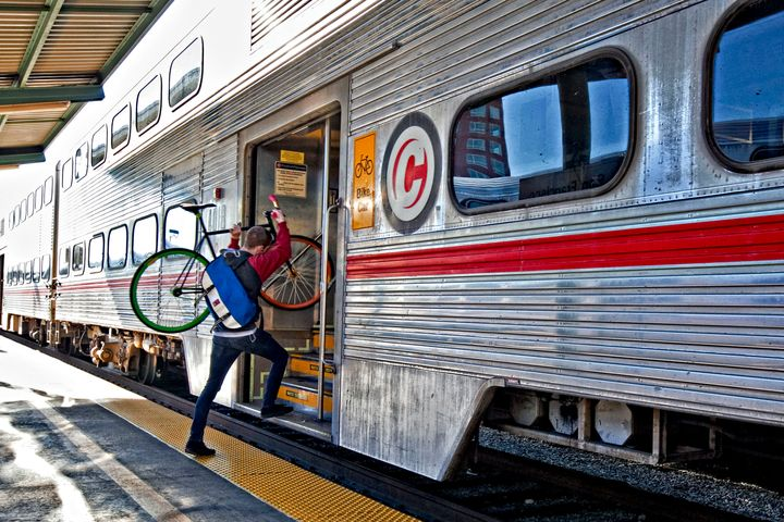 A commuter carries his bicycle aboard a Caltrain train in San Francisco on Nov. 24, 2009. Caltrain and the California High-Sp