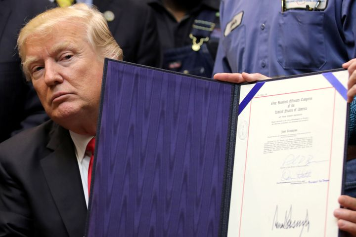 President Donald Trump shows Resolution 38, which nullifies the stream protection rule, after signing it at the White House&n
