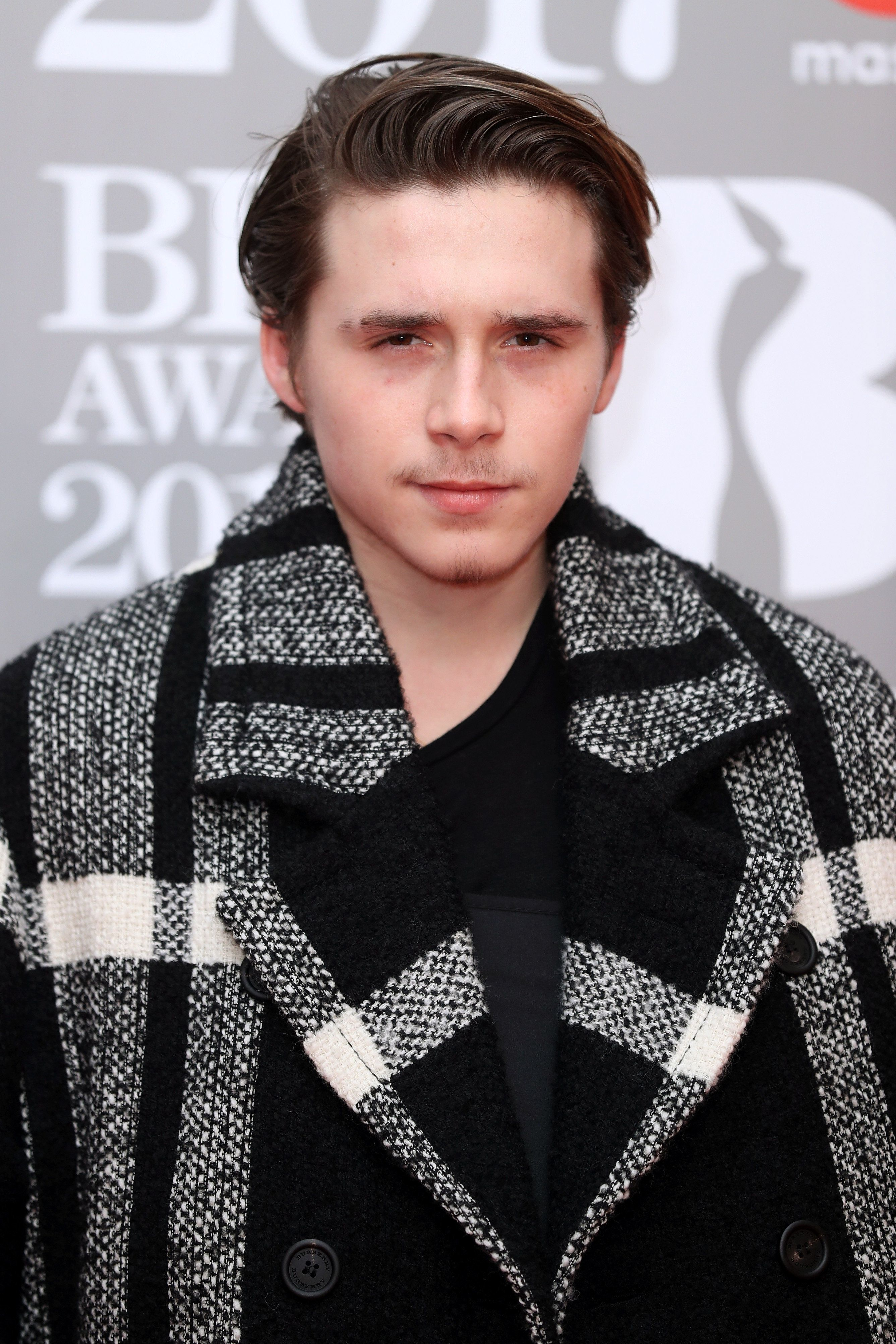 Brooklyn Beckham Hid His Snowboarding Injury Under A Burberry Coat At The Brit