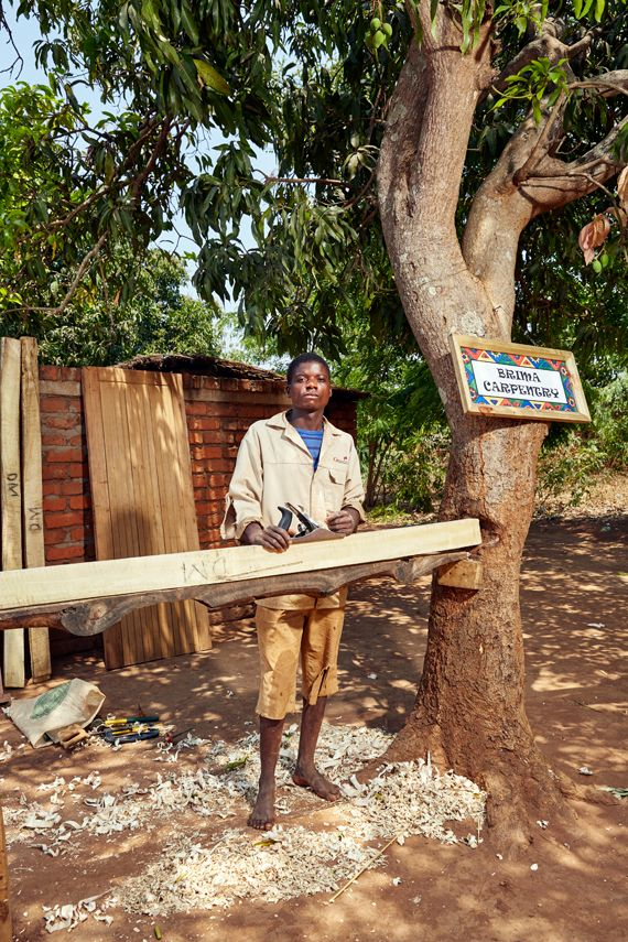 Laston Segula, 24 years old, stands in his carpentry workshop. Each entrepreneur decorates their stall or shop with a colourf