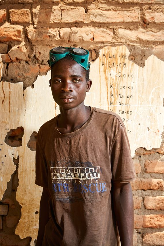 Raphael Bosa, 21 years old, wearing a pair of welding goggles, stands in the welding workshop he runs with his friend Geoffre