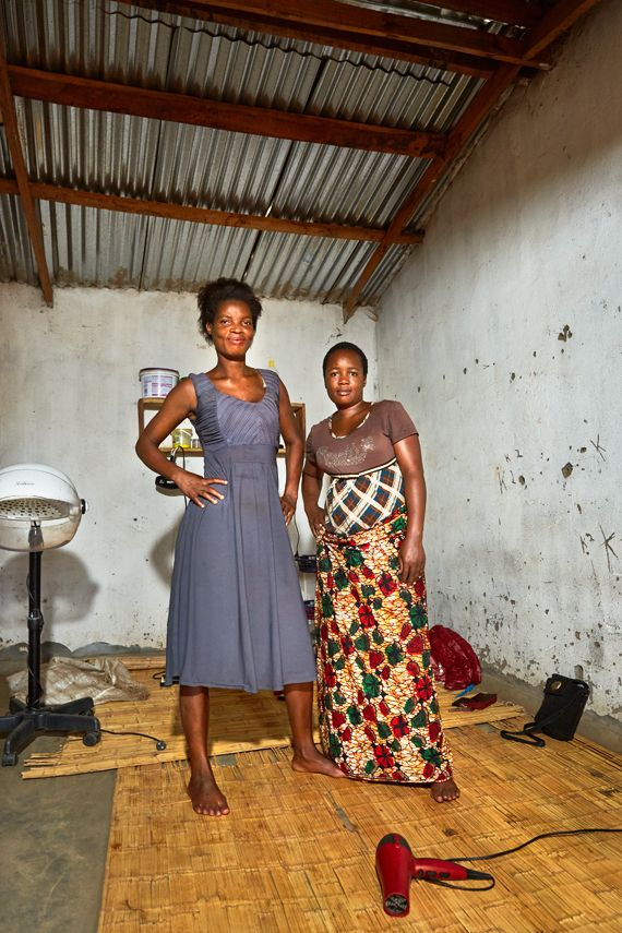 28 year old Esnat (left) and her business partner, Memory (right), stand in their hairdressing salon, Nomec,  near Luchenza,