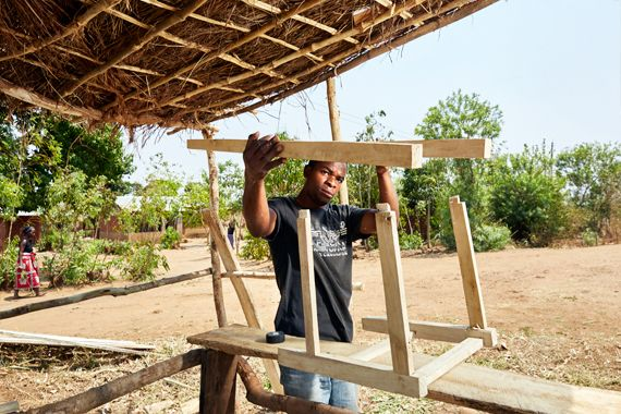 Blessings Kamanga, 23 years old, works on a chair, at his carpentry stall near Luchenza, southern Malawi. Blessings graduated
