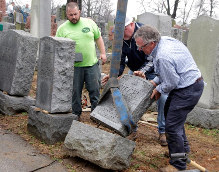 Spencer Pensoneau, Ron Klump and Philip Weiss of Weiss and Rosenbloom Monument company, work to right toppled Jewish headston