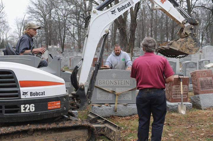 Volunteers from a local monument company help to reset vandalized headstones at Chesed Shel Emeth Cemetery on Wednesday