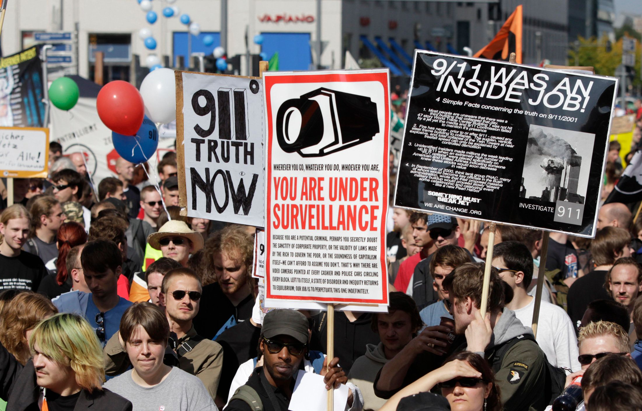 Conspiracy theorists hold signs and placards during a demonstration for data privacy in Berlin, September 11, 2010. REUTERS/Tobias Schwarz (GERMANY - Tags: POLITICS CIVIL UNREST SOCIETY)