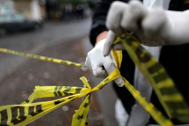 <p>A forensic technician ties a used police line together to seal off a crime scene in Monterrey. </p>
