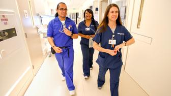 David Fuentes, 25, a student in the masters entry clinical nurse program at UCLA, makes the rounds with registered nurses Pamela Helms, center, and Heather Alfano,  inside the intensive care unit at UCLA Medical Center, Santa Monica on April 11, 2013.  Fuentes is doing an internship at the Medical Center and Alfano is one of his clinical instructors.  (Photo by Mel Melcon/Los Angeles Times via Getty Images)