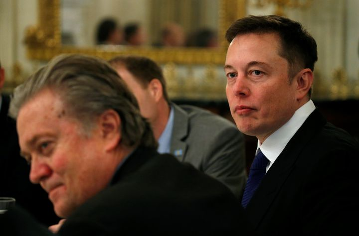 Tesla CEO Elon Musk (R) sits beside Senior Counselor to the President Steve Bannon (L) as U.S. President Donald Trump hosts a