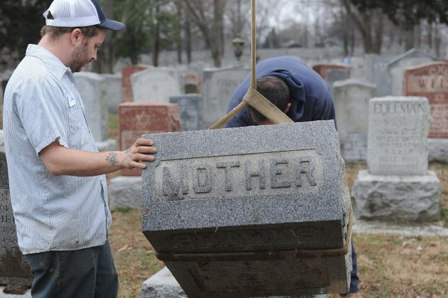 Volunteers from a local monument company help