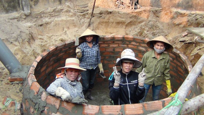 Vietnamese trained female masons construct biogas digesters.