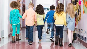 Rear view of a multi-ethnic group of seven children holding hands, walking down a school hallway together.  They are in kindergarten or preschool 4 to 6 years old.