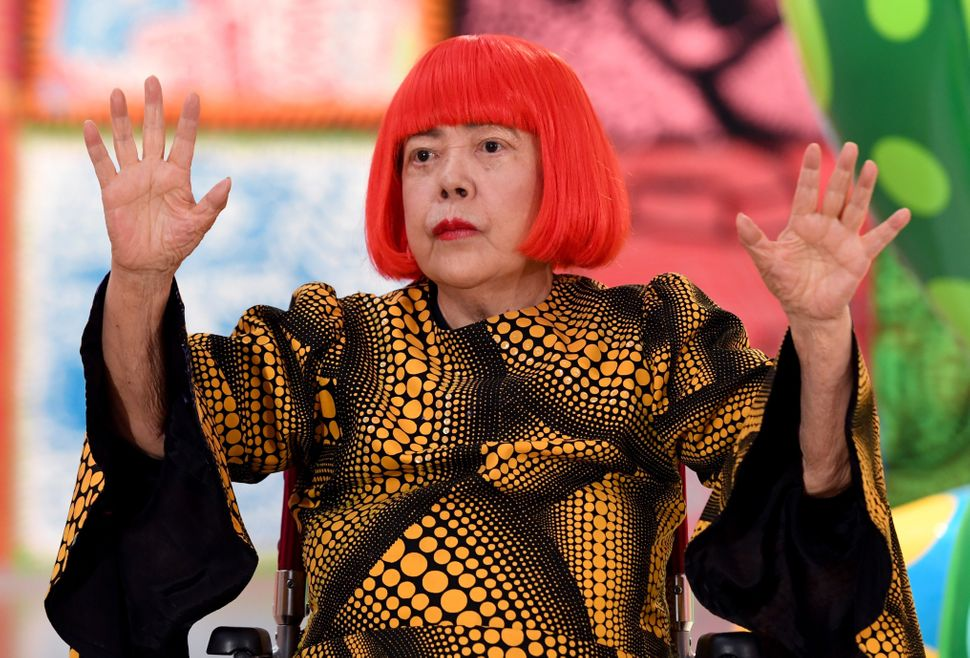 Japanese artist Yayoi Kusama waves at a photo session during a press preview in 2017.