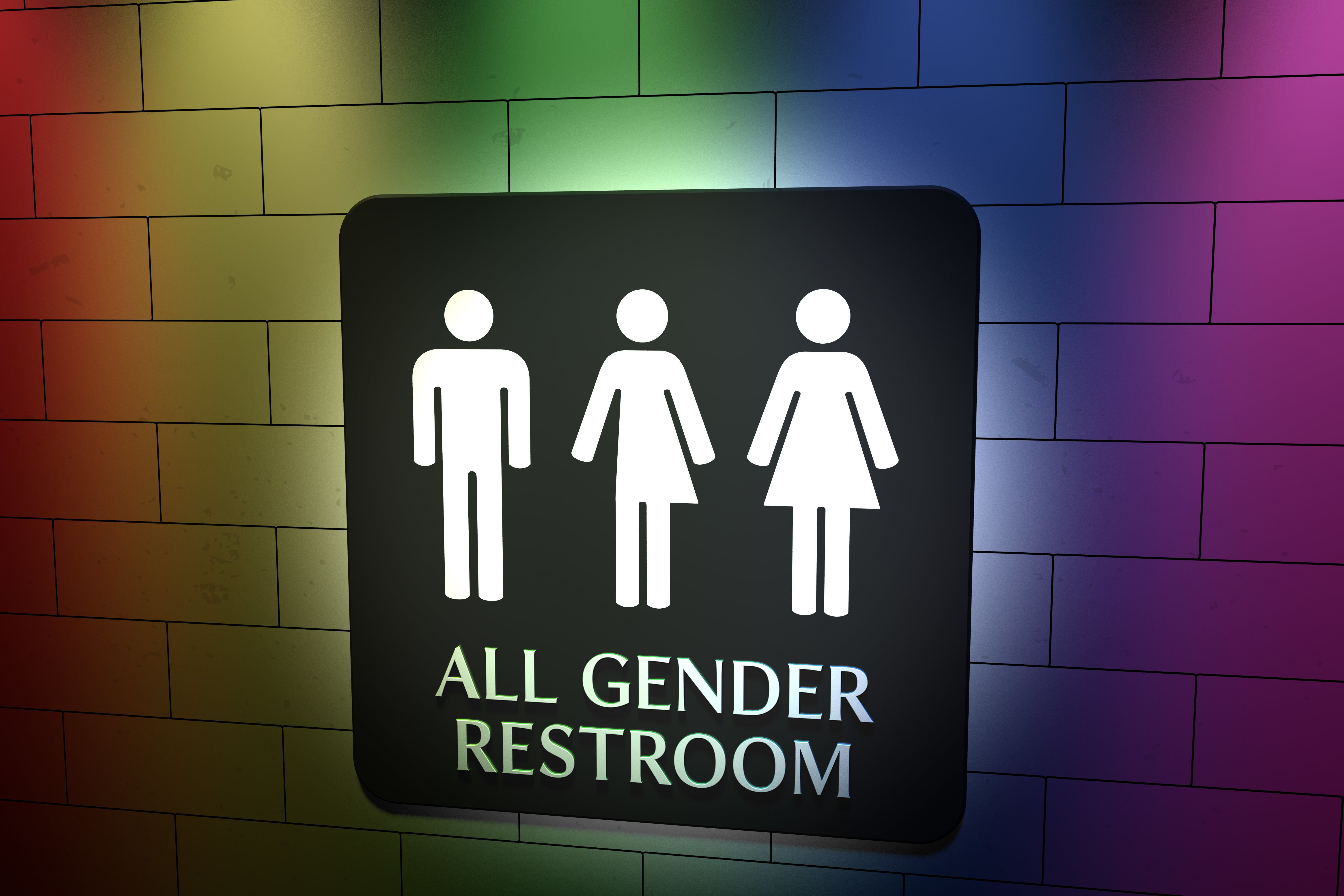 A sign on a wall for All Gender Toilets with symbols for men, trans and women. LGBT issue with pride coloured rainbow lights.
