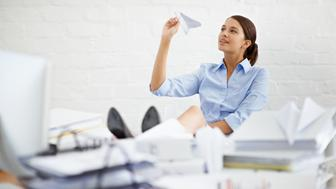 Shot of a young businesswoman throwing a paper plane while sitting at her desk