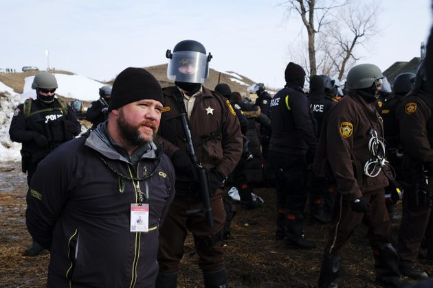 A man wearing a press ID steps in front of advancing law enforcement at the Ocetia Sakowin camp near...