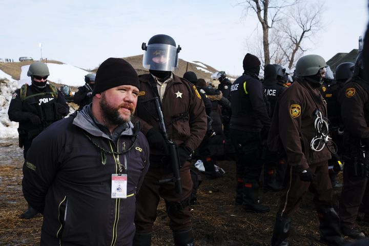 A man wearing a press ID steps in front of advancing law enforcement at the Ocetia Sakowin camp near a section of the Dakota