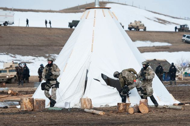 Officers inspect a tepee in while trying to clear Oceti Sakowin camp of several dozen protesters