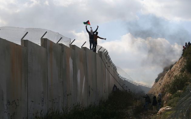 Palestinian protesters gesture as they climb an Israeli barrier in the West Bank village of Bilin near...