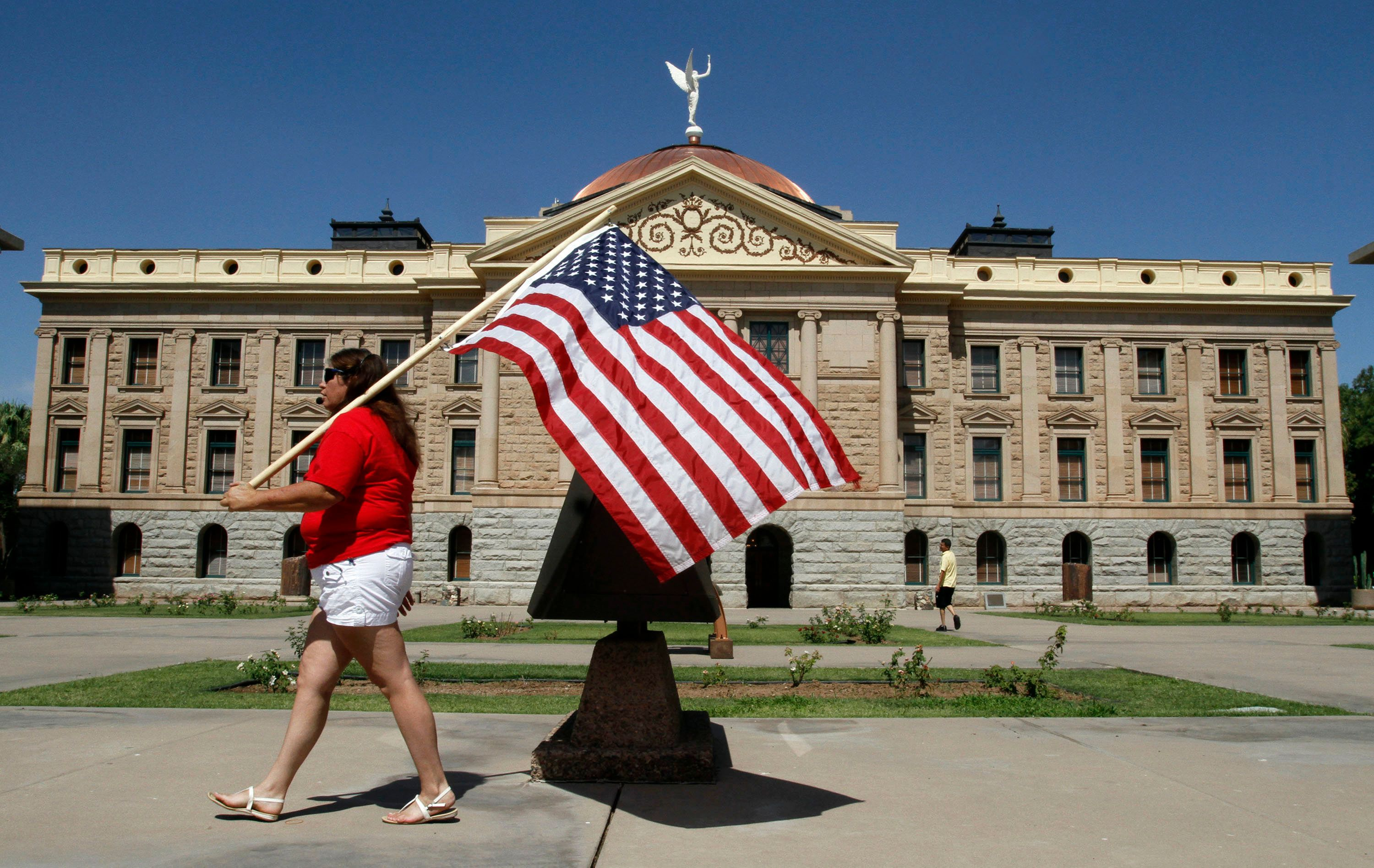 A protester marches around the Arizona State Capitol in Phoenix, Arizona, on June 25, 2012.