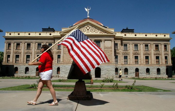 A protester marches around the Arizona State Capitol's grounds in 2012 after the Supreme Court upheld a key part of Arizona's