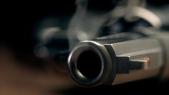 A gritty crime scene image of a smoking hand gun, revolver, lying on the floor with narrow focus on the tip if the barrel and dark background