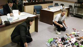Attorney Frank Totti  looks over papers while his client Frances Mountain sorts out Beanie Babies with her ex-husband Harold Mountain in Judge Gerald Hardcastle's Family Courtroom in Las Vegas November 5. The couple, who were divorced four months ago, were ordered to divide up the collection valued at $2,500 to $5000 but were unable to do so by themselves. The collection was ordered spread on the court floor and divided up one by one under the supervision of Family Court Judge Hardcastle. Maple the Bear was the first to go.    ??»