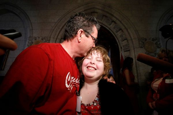Charlie Lowthian-Rickert, 10, who is transgender, is kissed by her father Chris on Parliament Hill in Ottawa, Canada, on May