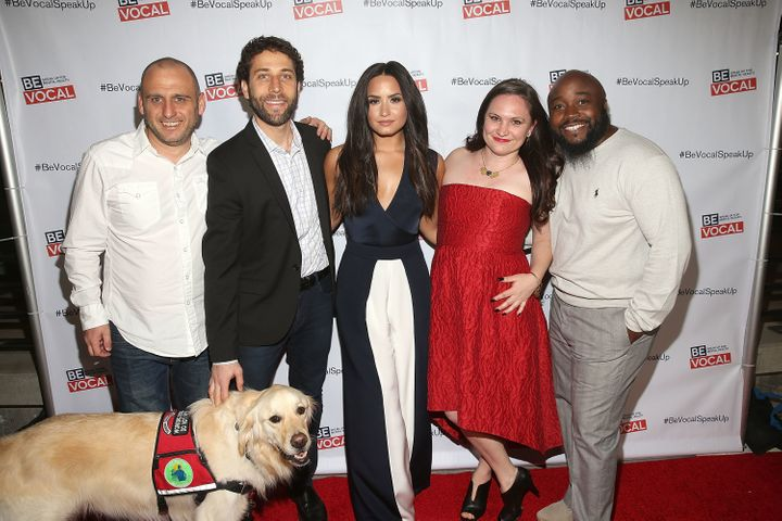 "Demi Lovato poses with the cast and crew of ""Beyond Silence,"" a documentary about three people who learned to live well"