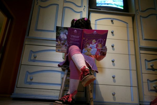 Lulu, a transgender girl, reads a book in her room at home in Buenos Aires on July 25, 2013. The 6-year-old Argentine child,
