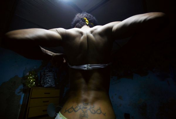 Julio Yoaris Alvarez adjusts his brassiere while getting dressed at his home in Havana, Cuba, on May 16, 2009. From an early