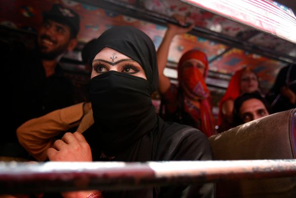 Some of several dozen detained Pakistani transgender people watch from a police bus as another transgender woman and a man ar