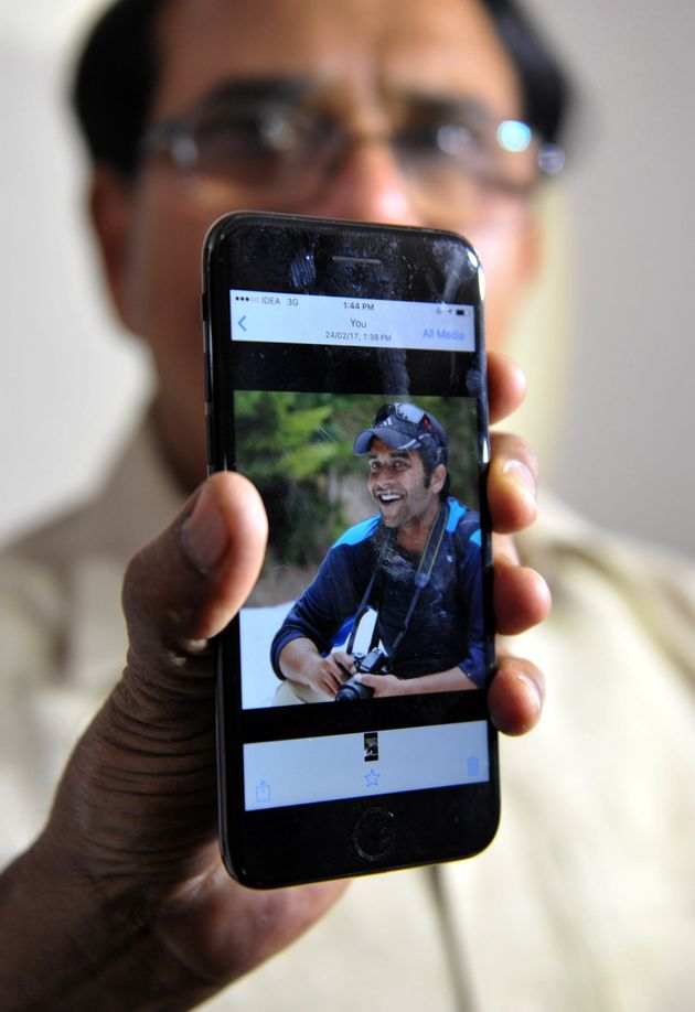 Alok Madasani's father holds up a smartphonewith an image of his son at his residence in Hyderabad...