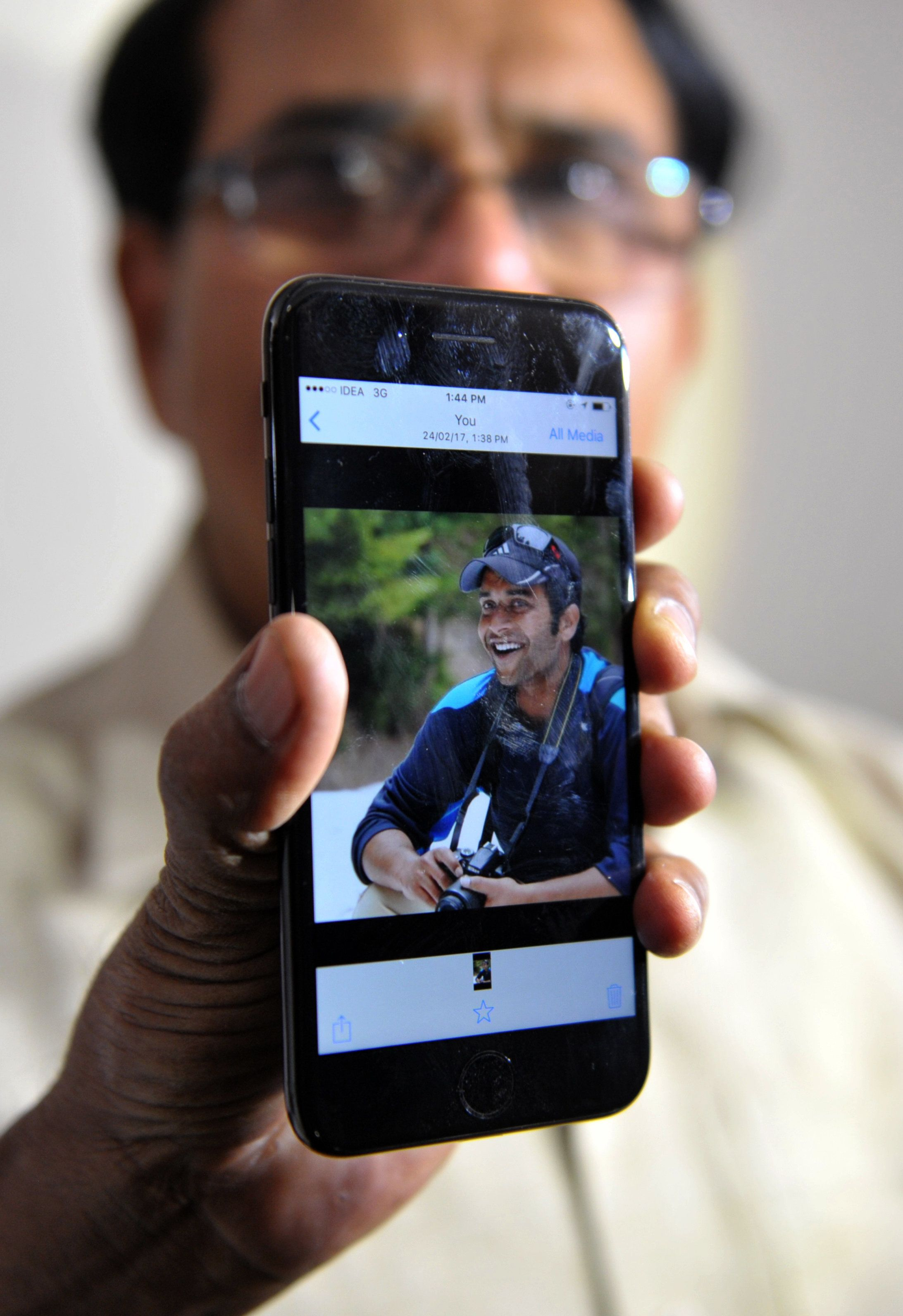 Alok Madasani's father holds up a smartphone with an image of his son at his residence in Hyderabad on Feb. 24, 2017.