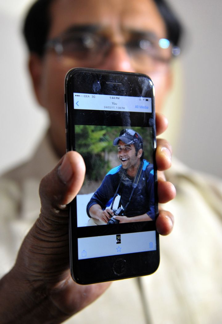 Alok Madasani's father holds up a smartphonewith an image of his son at his residence in Hyderabad on Feb. 24, 2017.