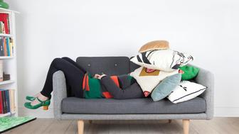 Woman lying on sofa with pile of pillows over her head.