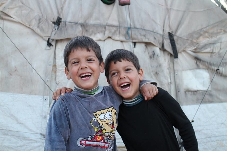 Twins, Ahmed and Mahmoud, laugh together in a refugee camp in