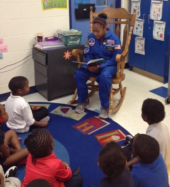 Taylor Richardson reads to a group of children.