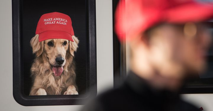 A man stands near a Donald Trump campaign vehicle with an image of a dog in a window before a campaign rally on Feb. 5,