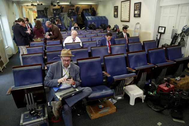 Glenn Thrush (L), chief White House political correspondent for the New York Times, works in the briefing...