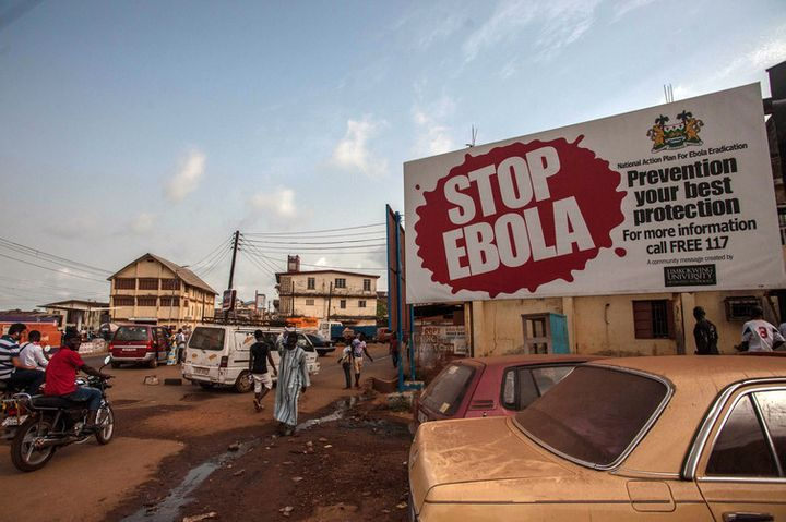 People pass a banner during Sierra Leone's Ebola free campaign in the city of Freetown, Jan. 15, 2016.