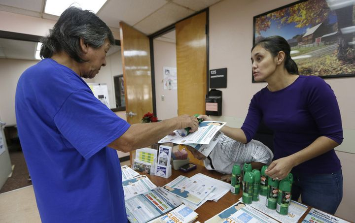 A worker at the Wynwood Community Service Center hands a local resident a can of insect repellent during the Zika scare, Aug