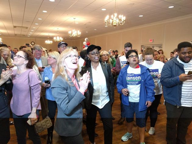 Democrat Stephanie Hansen, surrounded by volunteers, watches election results showing her victory in...