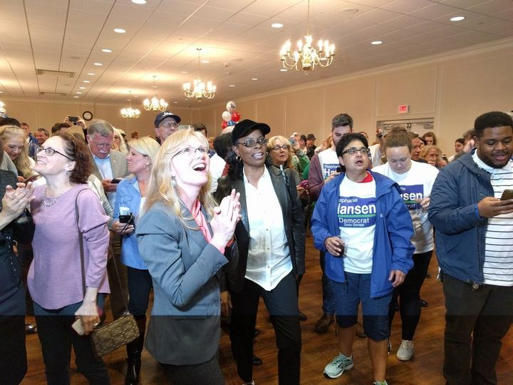 Democrat Stephanie Hansen, surrounded by volunteers, watches election results showing her victory in Saturday's special state