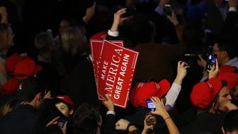 An attendee holds 'Make America Great Again' signs during an election night party for 2016 Republican Presidential Nominee Donald Trump at the Hilton Midtown hotel in New York, U.S., on Tuesday, Nov. 8, 2016. Fifty-one percent of voters nationally were bothered a lot by Trump's treatment of women, while Democrat Hillary Clinton's use of private e-mail while secretary of state was troubling to 44 percent, according to preliminary exit polling as voting neared a close in some states. Photographer: Andrew Harrer/Bloomberg via Getty Images